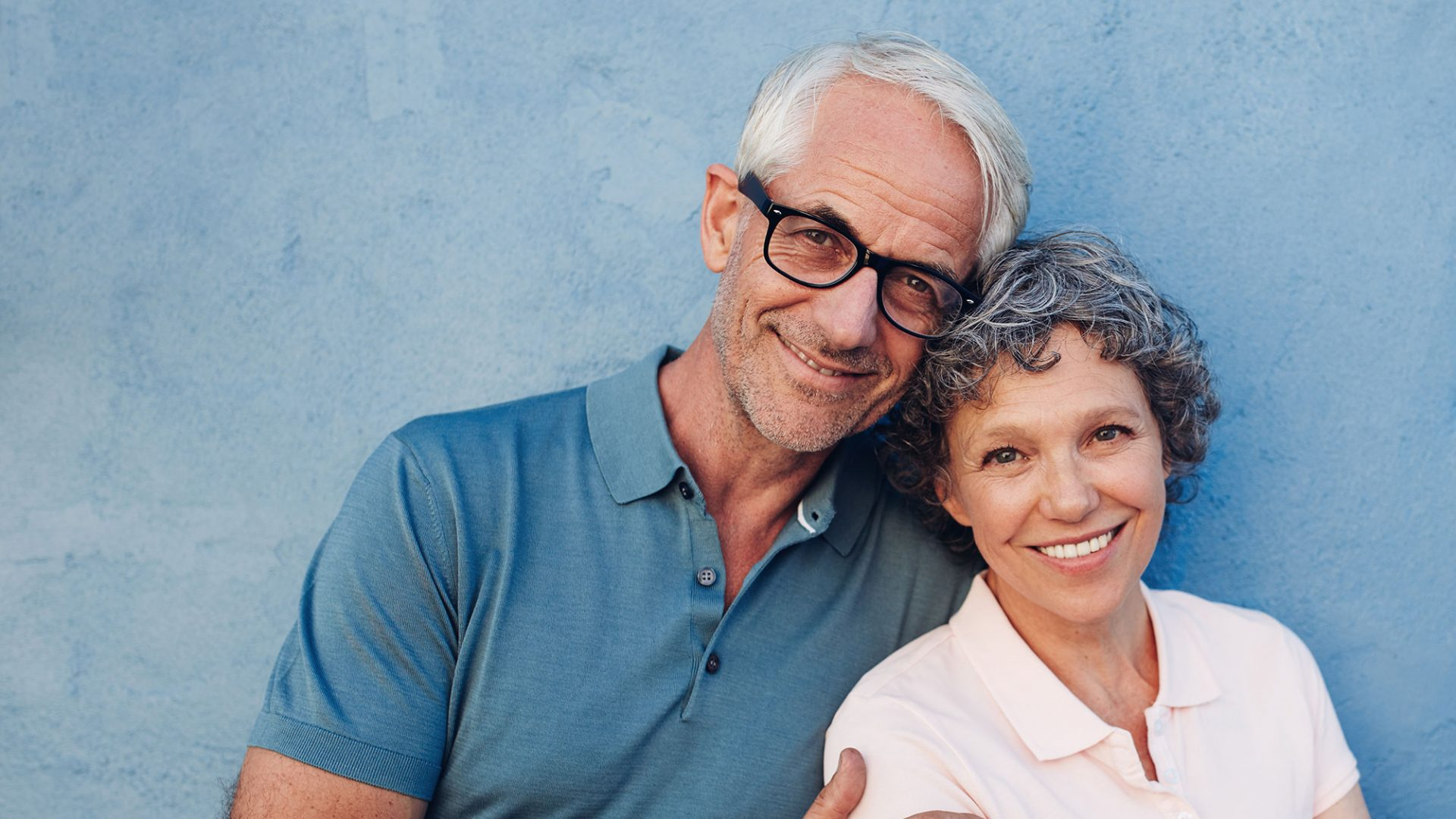 Middle aged couple standing against a textured wall and smiling