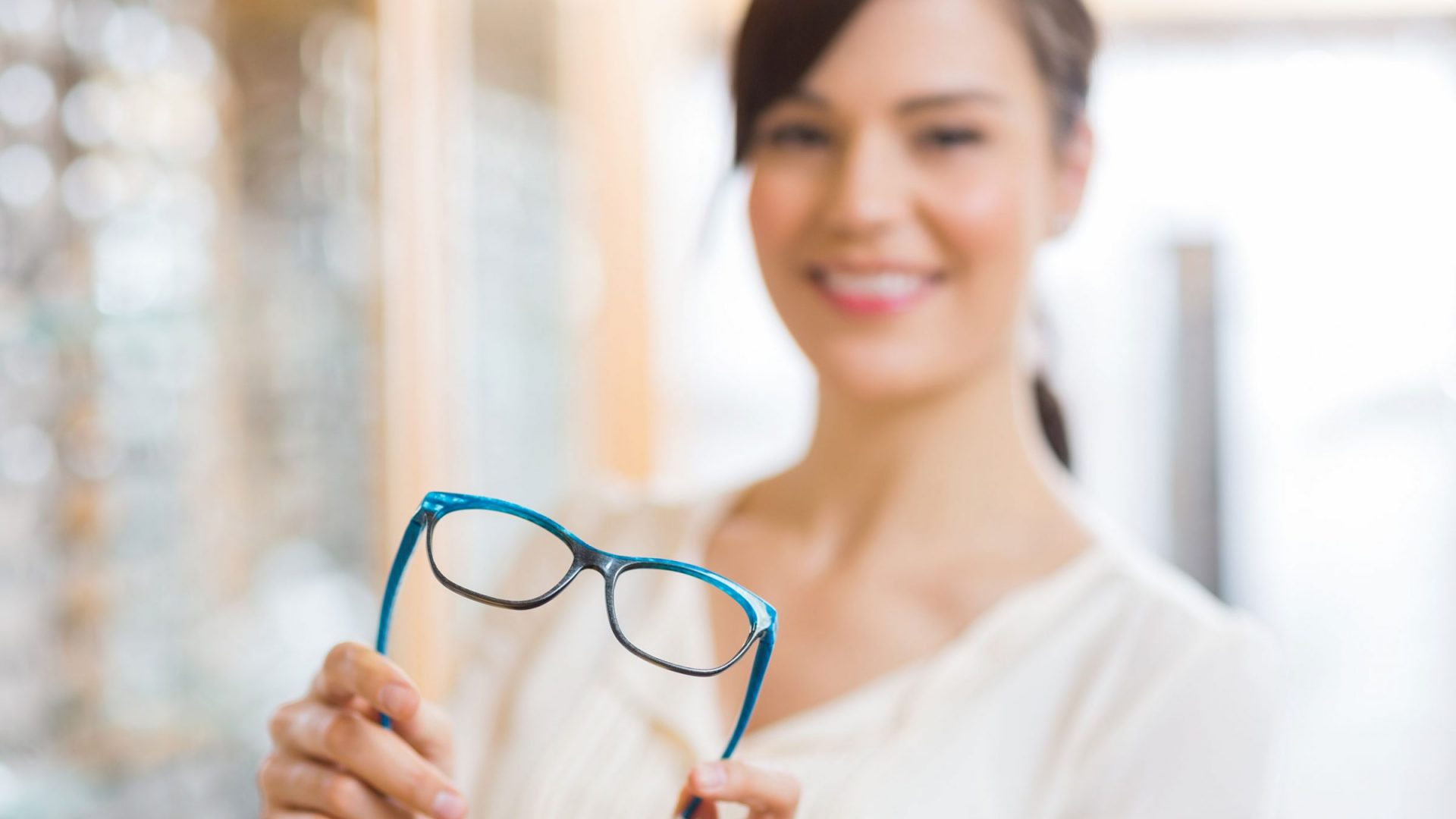 woman holding and trying on a pair of glasses