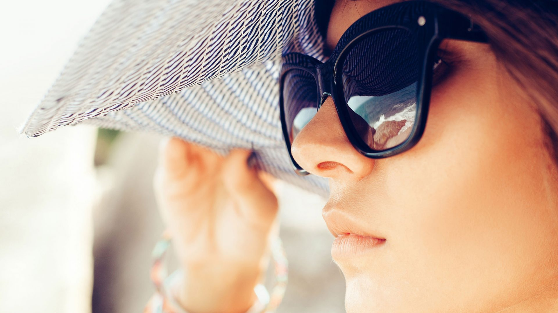 close-up of woman with sunglasses and big floppy hat